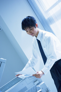 コピーを取るビジネスマンの写真素材 [FYI01321671]