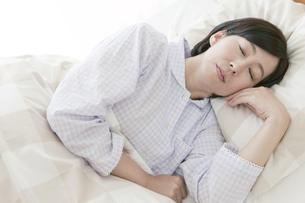 ベッドで眠る中高年女性の写真素材 [FYI01321672]
