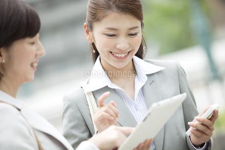 タブレットPCを見るビジネスウーマン2人の写真素材 [FYI01321848]