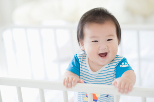 ベビーベッドで笑う赤ちゃんの写真素材 [FYI01321895]