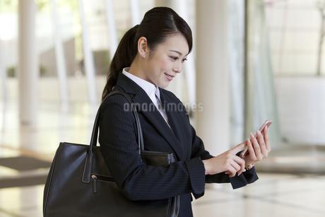 スマートフォンを見るビジネスウーマンの写真素材 [FYI01321996]