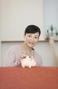 貯金箱にお金を入れる中高年女性の写真素材 [FYI01322121]