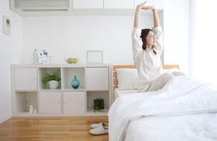 ベッドの上でストレッチをする女性の写真素材 [FYI01322220]