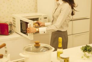 お弁当をレンジに入れる女性の写真素材 [FYI01322644]