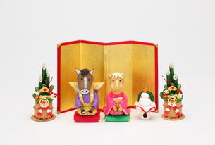 新年の挨拶する午のカップルと金屏風と角松の写真素材 [FYI01323458]