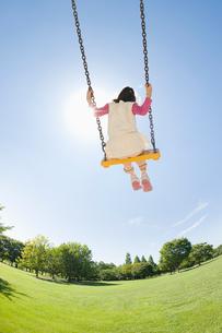 公園でブランコにのる女の子の写真素材 [FYI01323555]