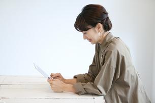 テーブルでタブレットPCを見る女性の写真素材 [FYI01323690]