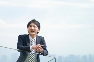 笑いながら遠くを見つめるビジネスマンの写真素材 [FYI01323754]