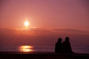 夕陽とカップルのシルエットの写真素材 [FYI01323762]
