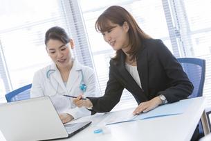 打ち合わせをする女医とビジネスウーマンの写真素材 [FYI01323863]