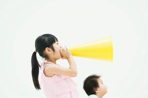 メガホンを持つ女の子と見上げる赤ちゃんの写真素材 [FYI01323951]