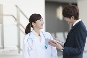 打ち合わせをするビジネスマンと女医の写真素材 [FYI01324095]