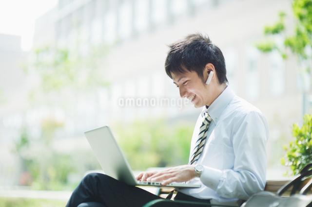 屋外でノートパソコンを操作するビジネスマンの写真素材 [FYI01324137]