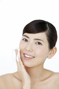 頬にコットンをあてる女性の写真素材 [FYI01324274]