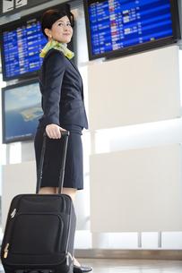 スーツケースを引くキャビンアテンダントの写真素材 [FYI01324410]