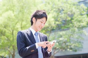スマートフォンを操作するビジネスマンの写真素材 [FYI01324456]