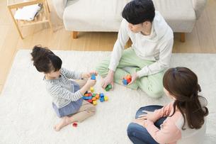 積み木で遊んでいる家族3人の写真素材 [FYI01324925]