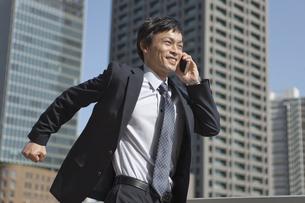 携帯電話で通話しながら走るビジネスマンの写真素材 [FYI01325061]