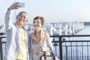 スマートフォンで写真を撮るシニア夫婦の写真素材 [FYI01325068]