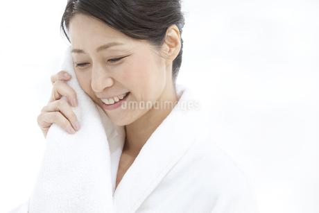 タオルを顔にあてる女性の写真素材 [FYI01325090]