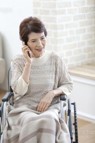スマートフォンで通話する車椅子のシニア女性の写真素材 [FYI01325091]