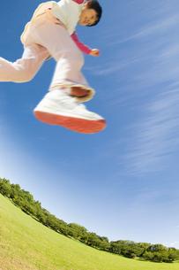 新緑の公園でジャンプする女の子の写真素材 [FYI01325225]