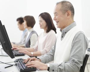 パソコン教室を受講する中高年グループの写真素材 [FYI01325368]