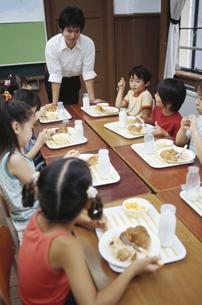 給食を食べる小学生と先生の写真素材 [FYI01325398]