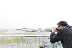 望遠鏡をのぞくビジネスマンの写真素材 [FYI01325434]