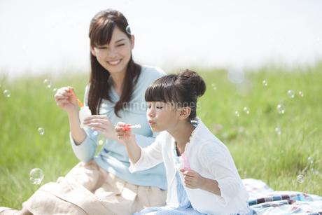 シャボン玉で遊ぶ親子の写真素材 [FYI01325444]