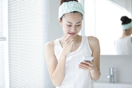 歯磨き中にスマートフォンを見る女性の写真素材 [FYI01325489]