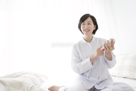 ベッドでスマートフォンを操作する中高年女性の写真素材 [FYI01325496]