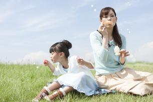 シャボン玉で遊ぶ親子の写真素材 [FYI01325505]
