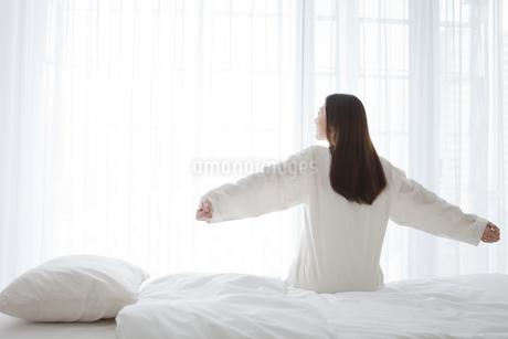 ベッドに座って伸びをする女性の写真素材 [FYI01325516]