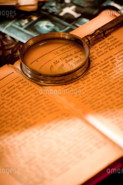 古書に置かれたルーペの写真素材 [FYI01325542]