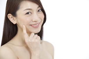 指で頬を触る女性の写真素材 [FYI01325566]