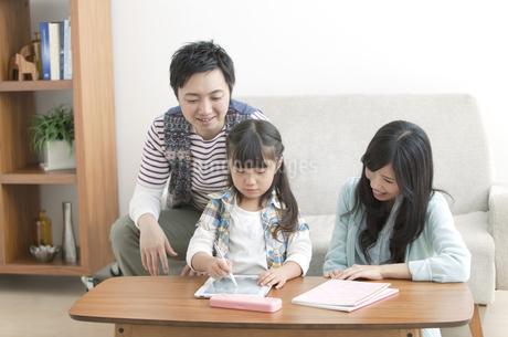タブレットPCを操作する女の子と両親の写真素材 [FYI01325578]