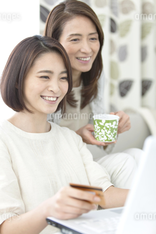 ネットショッピングをする娘と母の写真素材 [FYI01325648]
