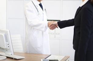 握手をする医者とビジネスウーマンの写真素材 [FYI01325853]