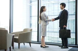 握手をするビジネスマンとビジネスウーマンの写真素材 [FYI01325933]