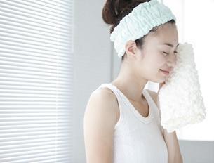 タオルで顔を拭く女性の写真素材 [FYI01325949]