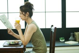 朝食中に新聞を読む女性の写真素材 [FYI01326216]