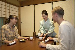 お茶を差し出す日本人女性と外国人カップルの写真素材 [FYI01326230]