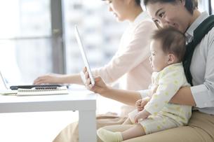 タブレットPCを見る赤ちゃんとビジネスウーマンの写真素材 [FYI01326327]