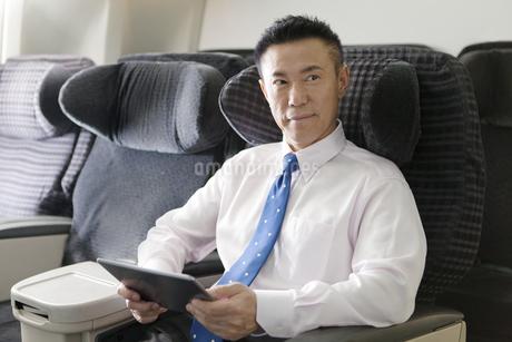 機内でタブレットPCを持つビジネスマンの写真素材 [FYI01326868]