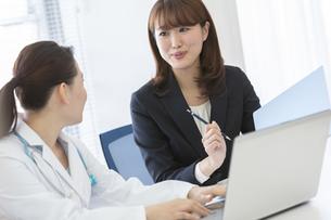 打ち合わせをする女医とビジネスウーマンの写真素材 [FYI01326876]