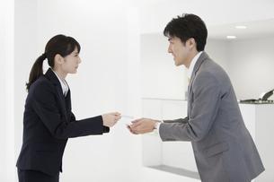 名刺交換するビジネスマンとビジネスウーマンの写真素材 [FYI01326934]