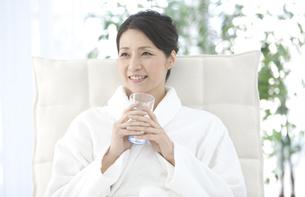 水を飲むバスローブの女性の写真素材 [FYI01327109]