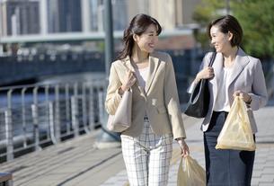 コンビニ袋を持つビジネスウーマン2人の写真素材 [FYI01327370]