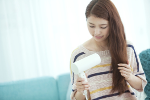 ドライヤーで髪を乾かす女性の写真素材 [FYI01327412]